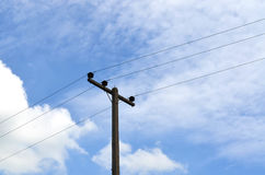 Electrical pole with power lines against hazy blue sky Royalty Free Stock Image
