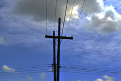 Electrical pole with power lines against hazy blue sky Stock Images