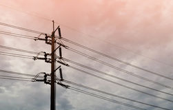 Electrical pole with power lines against orange sky Royalty Free Stock Photos