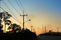 Electrical pole at Sunset on the rural road Stock Photos