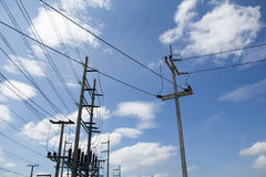 Electrical poles. Abstract Electrical poles of high voltage in white cloud and blue sky Royalty Free Stock Photo