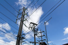 Electrical poles. Abstract Power line against the blue sky. Electrical poles of high voltage in white cloud and blue sky Royalty Free Stock Photo