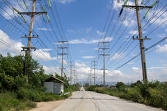 Electrical poles. Electric power line on road with sky background. Electricity poles and power cable with blue sky Stock Photo