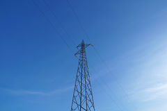 Electrical poles of high voltage in white cloud and blue sky Stock Photography