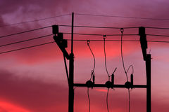 Electrical post. With power line cables against sunset Stock Photos