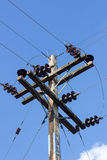 Electrical post by the road with power line cables, against blue Stock Image