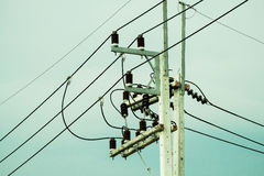 Electrical post by the road with power line cables, transformers and phone lines Royalty Free Stock Image