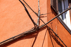 Electrical power cables, telephone cables, and metal water pipes in front of an old building facade Stock Images