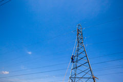 Electrical Power Cables Tower Repairs Electricians. Electrical power cables steel tower repairs done by Electricians against the blue sky royalty free stock photos