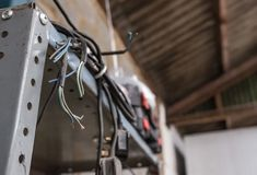 Electrical power cord, some with UK plugs seen hanging metal shelving in a workshop. stock photo