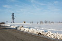 Electrical power line pillar on snow in front of blue sky stock photos