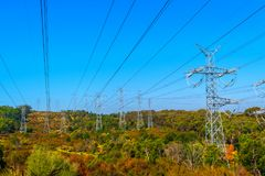 Electrical power lines over the hills and forest royalty free stock photography
