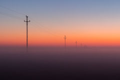 Electrical Power Lines and Pylons disappear over the horizon with Misty Sunrise, Sunset Royalty Free Stock Photos