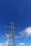 Electrical power lines in sky. Electrical power lines and pylon in deep blue cloudy sky Royalty Free Stock Images