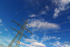 Electrical power lines in sky. Electrical power lines and pylon in deep blue cloudy sky, declined, horizontal Stock Photos