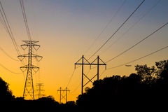 Electrical power lines stand silhouetted by an orange sunset. Stock Photo