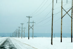 Electrical power lines in winter. With snow covered fields Royalty Free Stock Photo