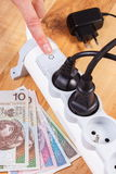 Electrical power strip with connected plug and polish currency money, energy costs. Finger of woman turns off electrical power strip with connected plug, polish Royalty Free Stock Image