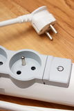 Electrical power strip with switch on-off on wooden floor. Electrical extension, power board Royalty Free Stock Photos