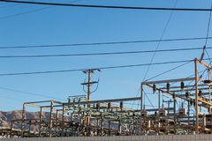 Electrical power transfer station against mountain range, blue sky. Copy space, horizontal aspect Royalty Free Stock Photography