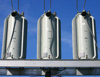 Electrical Power Transformers. Three electrical power transformers installed on a platform and cabled in, shot against a blue sky royalty free stock images