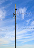 Electrical Power Transmission Lines. High intensity electrical power lines and tower used to distribute electrical energy, against a blue sky with wispy clouds Royalty Free Stock Images