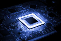 Electrical processor. Glowing modern processor. Big illuminated graphic processor surrounding by other electrical components. Special tone image. Low aperture royalty free stock image