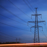 Electrical pylon and high voltage power lines at night. Royalty Free Stock Images