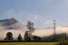 Electrical pylons in foggy countryside Royalty Free Stock Photo
