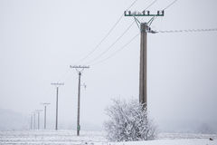 Electrical pylons high voltage wires in winter covered snow Stock Photo