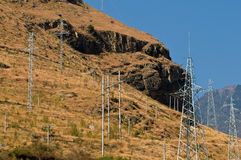 Electrical Pylons on hillside. A group of electrical pylons at a remote hillside location in China Royalty Free Stock Photo