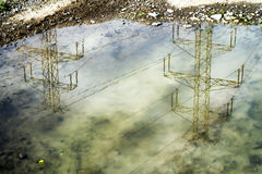 Electrical pylons reflexion. Electrical tower pylons reflection in a puddle Stock Photos