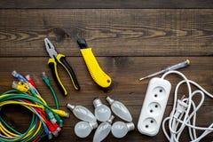 Electrical repair. Bulbs, socket outlet, cabel, screwdriver, pilers on dark wooden background top view copy space. Electrical repair. Bulbs, screwdriver, pilers royalty free stock image