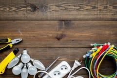 Electrical repair. Bulbs, socket outlet, cabel, screwdriver, pilers on dark wooden background top view copy space. Electrical repair. Bulbs, screwdriver, pilers royalty free stock photo