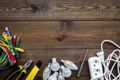 Electrical repair. Bulbs, socket outlet, cabel, screwdriver, pilers on dark wooden background top view copy space. Electrical repair. Bulbs, screwdriver, pilers stock image