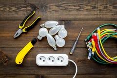 Electrical repair. Bulbs, socket outlet, cabel, screwdriver, pilers on dark wooden background top view copy space. Electrical repair. Bulbs, screwdriver, pilers stock images