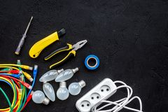 Electrical repair. Bulbs, socket outlet, cabel, screwdriver, pilers on black background top view copy space. Electrical repair. Bulbs screwdriver pilers top view royalty free stock photos