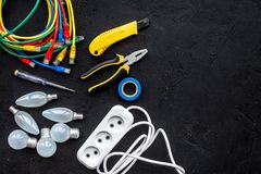 Electrical repair. Bulbs, socket outlet, cabel, screwdriver, pilers on black background top view copy space. Electrical repair. Bulbs screwdriver pilers top view stock image