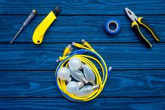 Electrical repair. Bulbs, socket outlet, cabel, screwdriver, pilers on blue wooden background top view copy space. Electrical repair. Bulbs screwdriver pilers stock photos