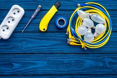 Electrical repair. Bulbs, socket outlet, cabel, screwdriver, pilers on blue wooden background top view copy space. Electrical repair. Bulbs screwdriver pilers royalty free stock image