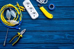 Electrical repair. Bulbs, socket outlet, cabel, screwdriver, pilers on blue wooden background top view copy space. Electrical repair. Bulbs screwdriver pilers stock image