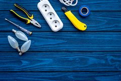 Electrical repair. Bulbs, socket outlet, cabel, screwdriver, pilers on blue wooden background top view copy space. Electrical repair. Bulbs screwdriver pilers royalty free stock photos