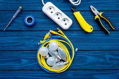 Electrical repair. Bulbs, socket outlet, cabel, screwdriver, pilers on blue wooden background top view copy space. Electrical repair. Bulbs screwdriver pilers royalty free stock photo