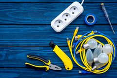 Electrical repair. Bulbs, socket outlet, cabel, screwdriver, pilers on blue wooden background top view copy space. Electrical repair. Bulbs screwdriver pilers royalty free stock photography