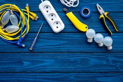 Electrical repair. Bulbs, socket outlet, cabel, screwdriver, pilers on blue wooden background top view copy space. Electrical repair. Bulbs screwdriver pilers royalty free stock images