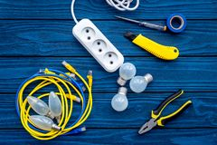 Electrical repair. Bulbs, socket outlet, cabel, screwdriver, pilers on blue wooden background top view. Electrical repair. Bulbs screwdriver pilers top view stock photos