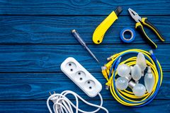 Electrical repair. Bulbs, socket outlet, cabel, screwdriver, pilers on blue wooden background top view copy space. Electrical repair. Bulbs screwdriver pilers stock photo