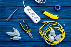 Electrical repair. Bulbs, socket outlet, cabel, screwdriver, pilers on blue wooden background top view. Electrical repair. Bulbs screwdriver pilers top view stock images