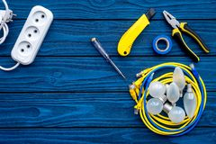 Electrical repair. Bulbs, socket outlet, cabel, screwdriver, pilers on blue wooden background top view copy space. Electrical repair. Bulbs screwdriver pilers stock photography