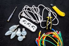 Electrical repair. Bulbs, socket outlet, cabel, screwdriver, pilers on black background top view. Electrical repair. Bulbs screwdriver pilers top view stock photo